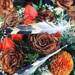 Blumenstrauß mit braunen Rosen und Federn